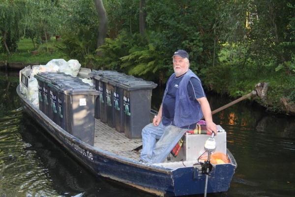 """Lübbenauer Ortsteil Lehde. Dieter Adler transportiert mit seinem speziellem Wasserfahrzeug die Mülltonnen und """"gelben Säcke"""" im Lagunendorf ab."""